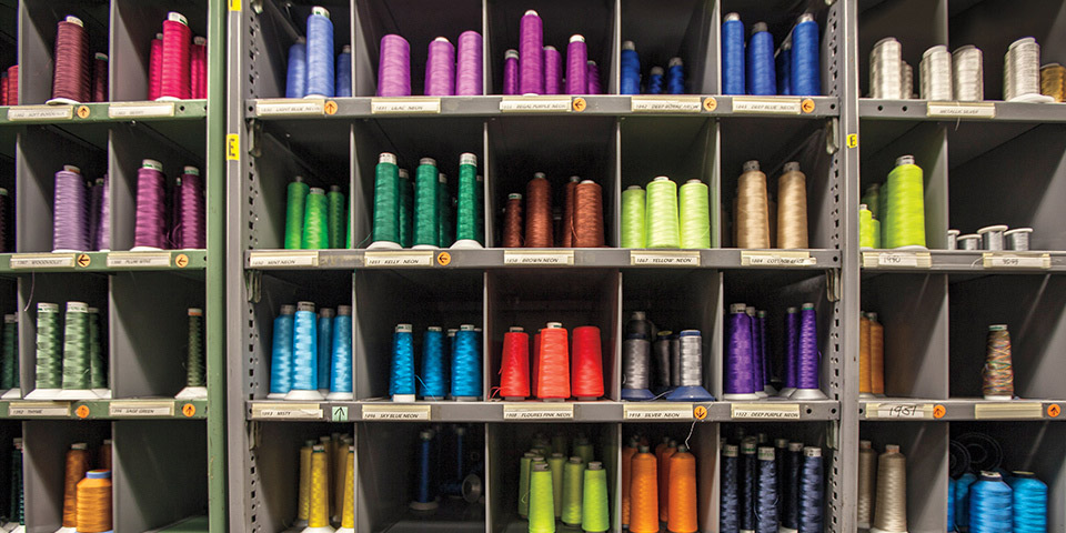 A shelf of a rainbow of different colored spools of thread used to make custom embroidery and monograms.