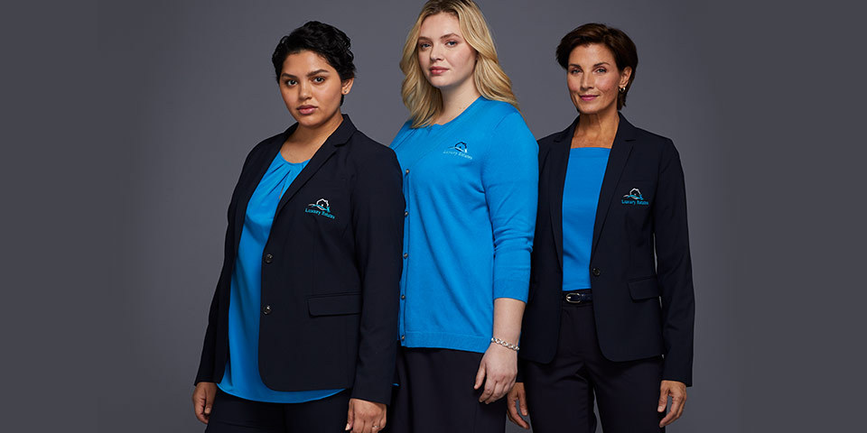 Three women wearing similar apparel with logo embroidery of their organization.