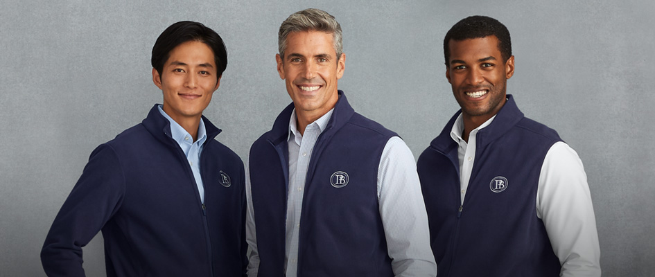 Three men wear navy fleece vests and jackets as they smile.