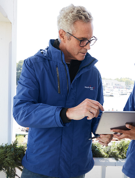 An older man with thick rimmed glasses wears a blue Squall System shell jacket as he looks at a tablet.