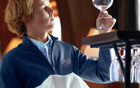 A man wearing a sweater looks to his left and up at a class of wine he holds into the light.
