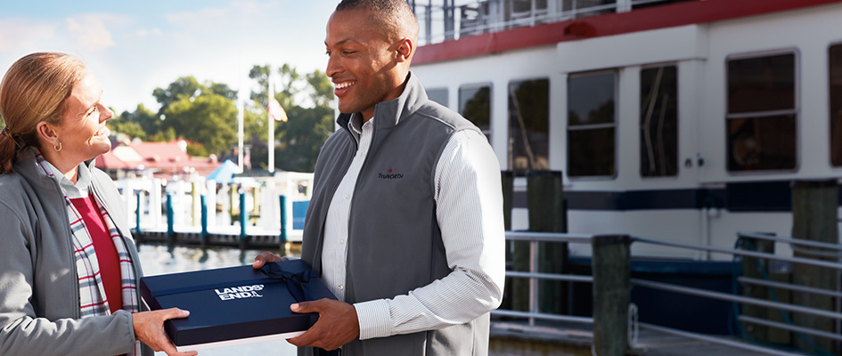 A man in a fleece vest hands a Lands' End gift box to a woman.
