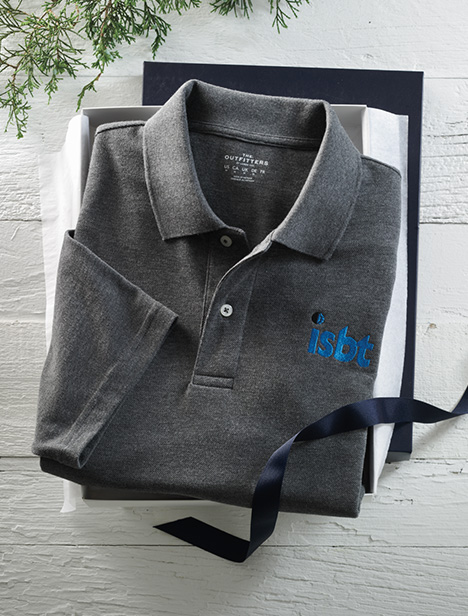 A gray polo lays inside an open gift box.
