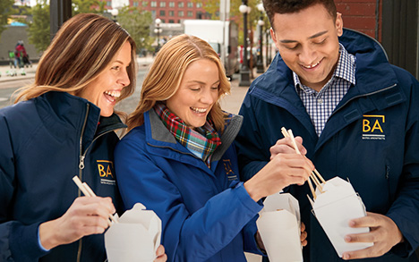 A man and two women are outside wearing jackets embroidered with their company logo as they share carryout food with chopsticks.
