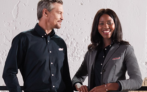 A mand and a woman stand together wearing black button down dress shirts.