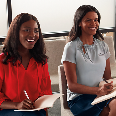 Two women are smiling while they take notes. Both are wearing blouses from Lands' End.