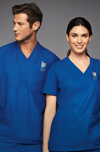 A man and a woman are both wearing blue scrubs uniforms with custom logo embroidery over their left chest.