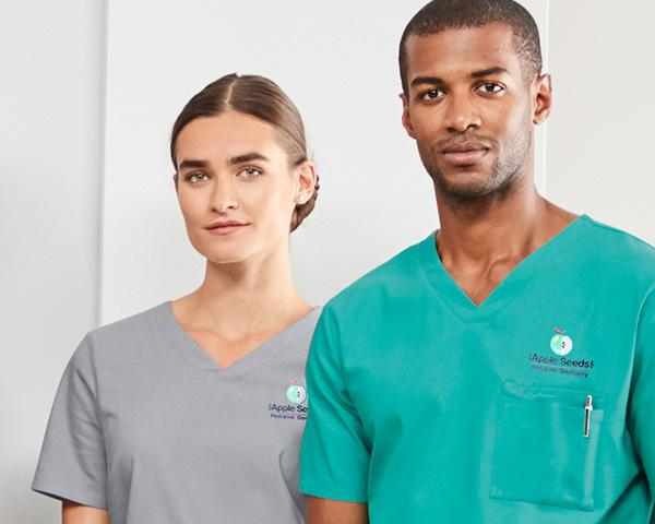 Two people wearing scrub uniforms.