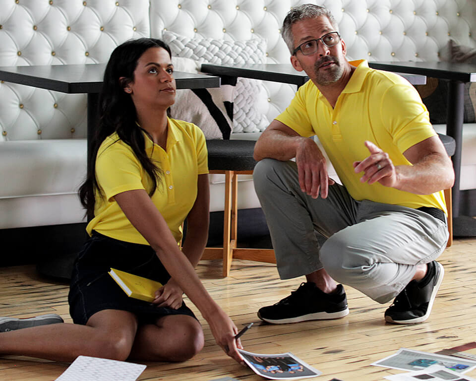 A man and a women working from home wearing yellow polos.