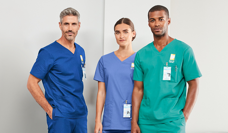 Three medical workers in scrubs.