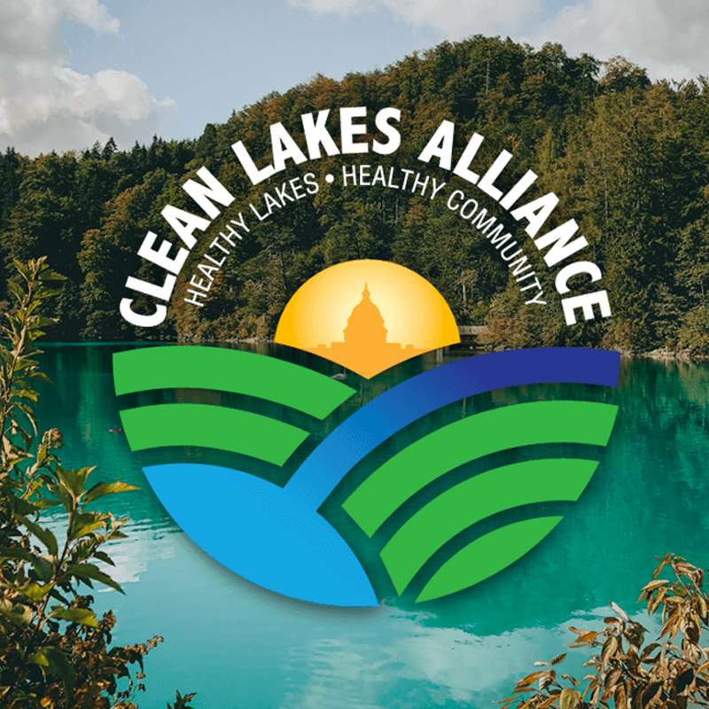 The Clean Lakes Alliance logo is laid on top of a scenic view of green trees and a clear blue lake.