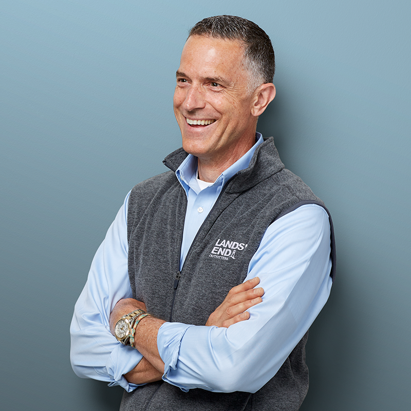 A photograph of Joe Ferreri, the Lands' End Business SVP, crossing his arms and smiling broadly while wearing a Lands' End Business light blue button down dress shirt and an embroidered heather gray vest.