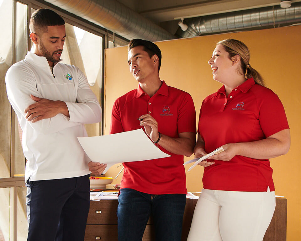 Employees from two different companies discuss a business plan while wearing polos.