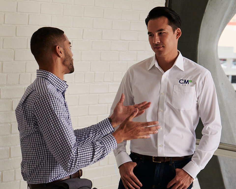 Two men in dress shirts discussing a business partnership.