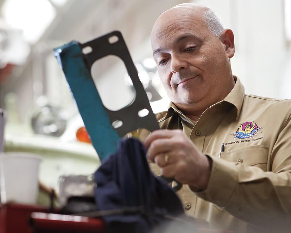 A man wearing a twill shirt fixes his machinery.