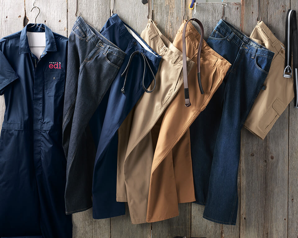 A collection of work pants hung on a wall.