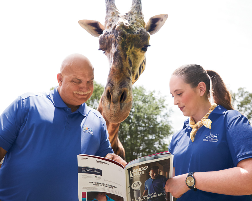 A man, a woman and a giraffe look at a Lands' End Business catalog.