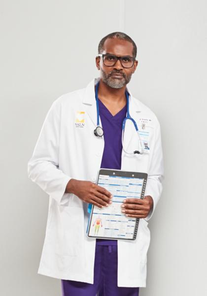 A man wearing deep purple scrubs.