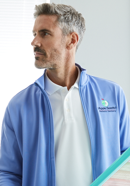 A man looks off to his right while wearing a white polo with a light blue jacket layered on top that sports his organizations logo embroidered on his left chest.