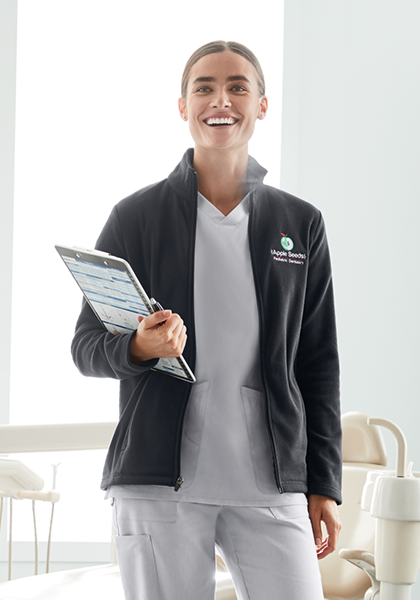 Woman in harbor gray scrubs layers on a charcoal gray fleece with custom logo embroidery on it.