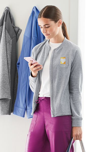 A woman wearing persian plum scrubs pants and a light gray fleece top with custom logo embroidery looks down at her phone as she prepares to leave work.
