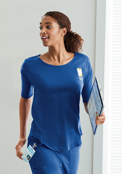 A woman wearing dark cobalt blue scrubs with custom logo embroidery on the left chest walks down a hall with a clipboard in hand and her ID badge clipped to her pants.