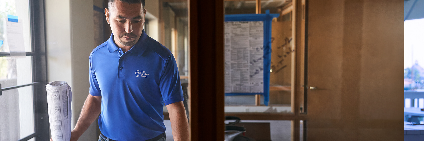 A man working in his office wearing a blue polo.