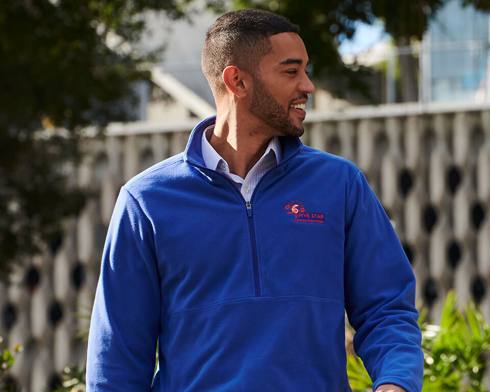 A man wearing a blue fleece jacket takes a brisk walk.