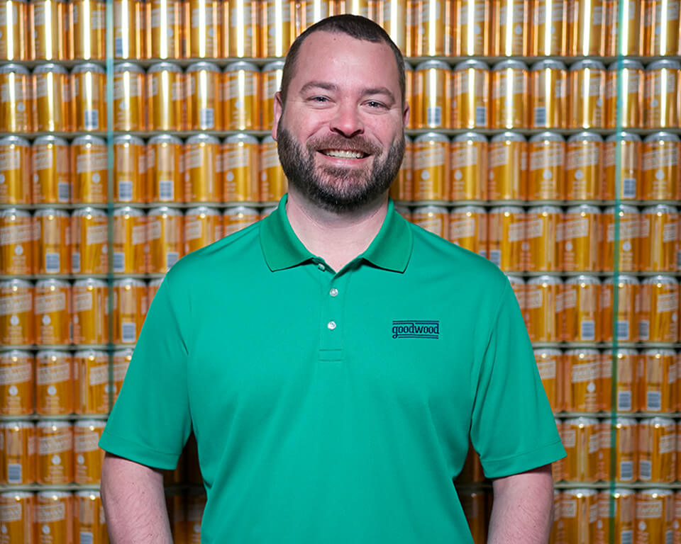 A man wearing a polo in front of a wall of stacked beverage cans.