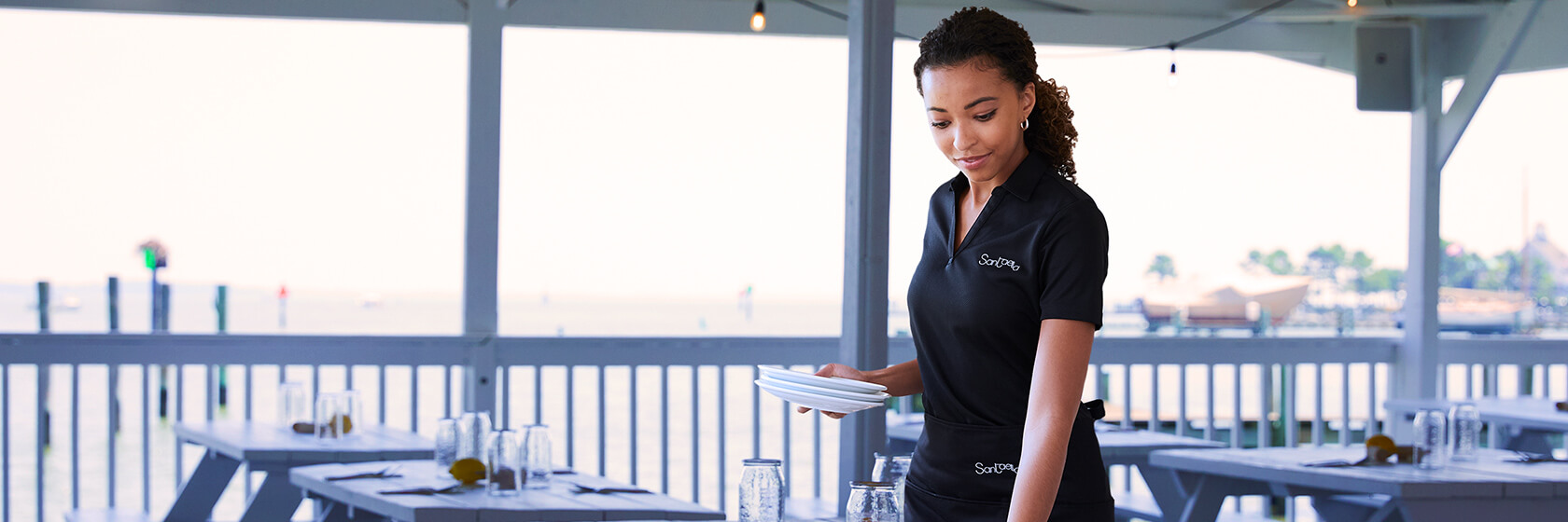 A woman wearing a black active polo working in a restaurant.