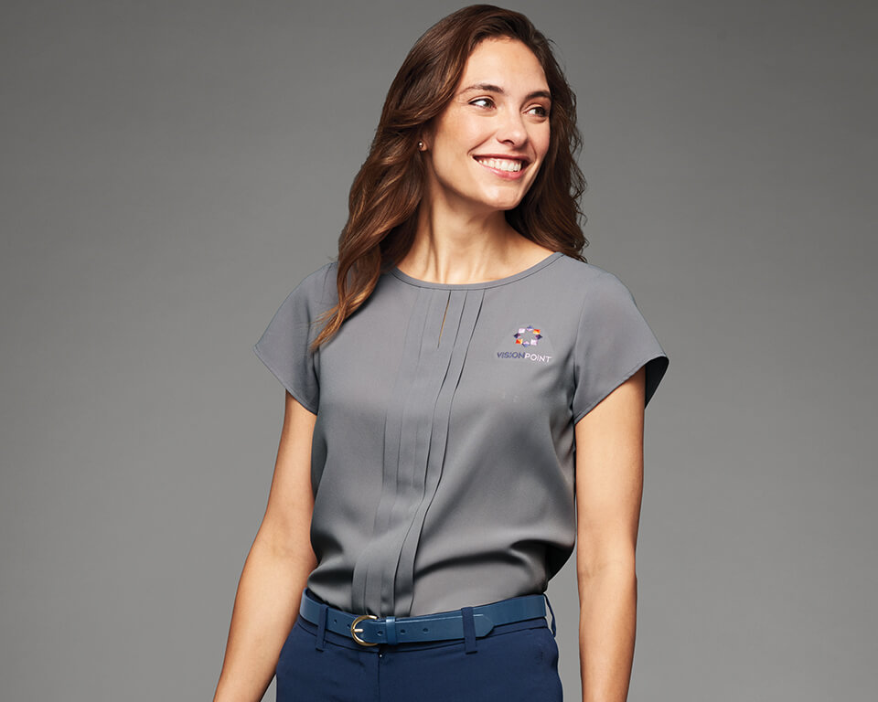 A woman wearing a gray soft blouse smiles at the camera.