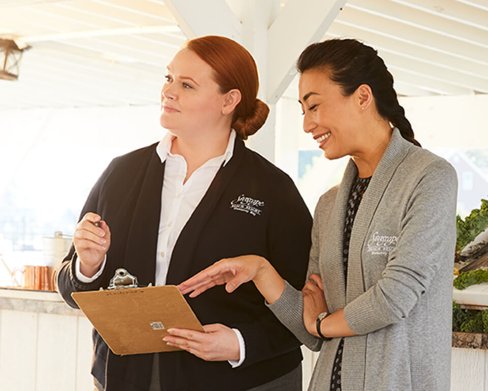 A woman wearing a sweater holds a clipboard while discusses a project with another woman.